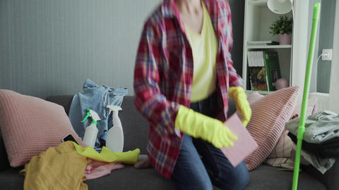 Exhausted woman in gloves sitting on sofa, relaxing after house cleaning work Live Action