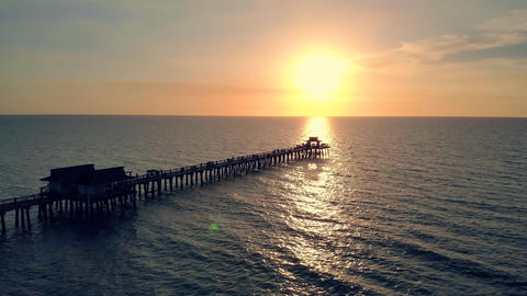 Sunset over the Gulf of Mexico, flying above pier Live Action