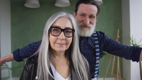 Good-looking positive happy modern mature couple posing on camera while bearded Live Action