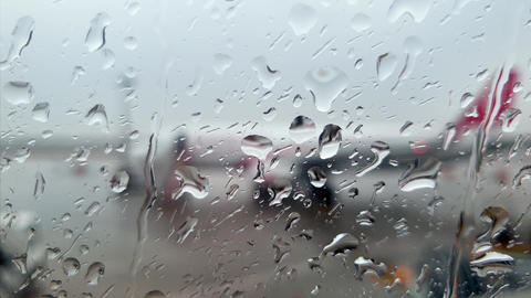 Closeup 4k video of rain droplets falling on wet airplane porthole in airplane Live Action