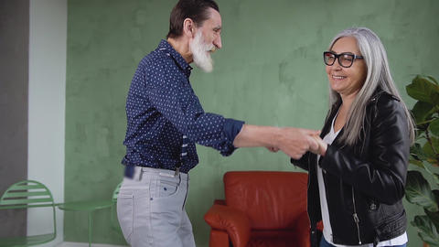 Positive cheerful loving senior husband and wife dancing together and having fun Live Action