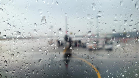 4k video through wet window on wet airplanes and airport terminal during rain Live Action