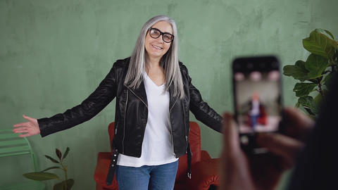 Smiling adorable modern trendy woman in glasses taking photo on phone of Live Action
