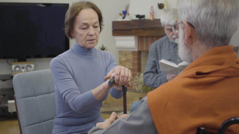 Grey-haired Caucasian mature man calming down old woman with walking stick Live Action
