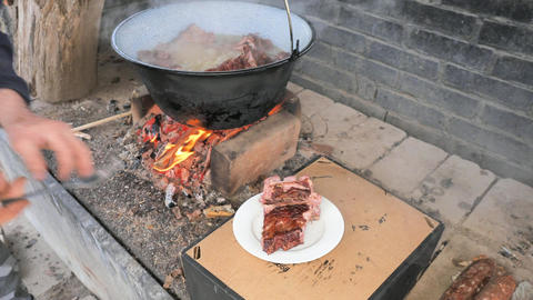 Freshly cooked meat on a porcelain plate. Finished meat in cauldron over fire on grill Live Action