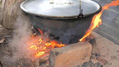 Cooking actions with black enamel cauldron or cooking pot used for outdoor cooking over an open Live Action