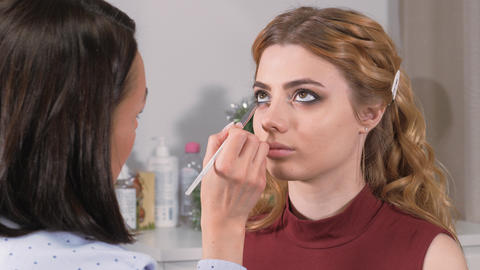 Applying makeup. Giving the eyes of the young girl's expression. Stroke the eye contour with a Live Action