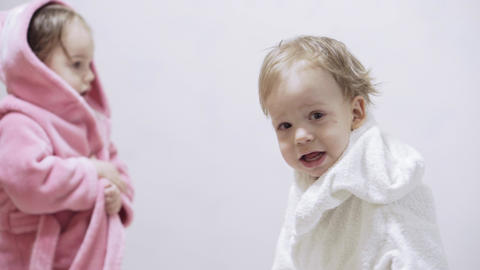 Two kids in bathrobes on a white background with wet hair after taking a bath Live Action