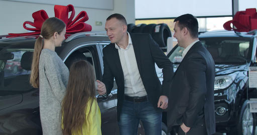 Positive Caucasian car dealer welcoming young couple with daughter in dealership Live Action