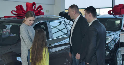 Trader in dealership talking to young Caucasian woman choosing vehicle with Live Action