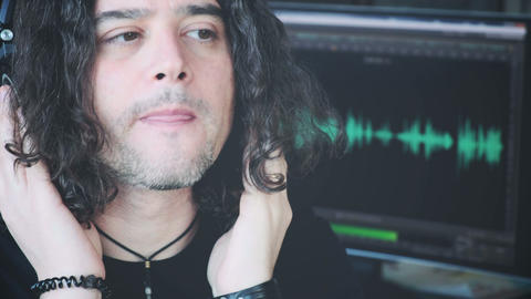 rock music composer with headphones focusing on audio software pc screen Live Action