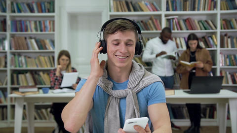 Joyful attractive modern young man in casual clothes sitting in the library and Live Action
