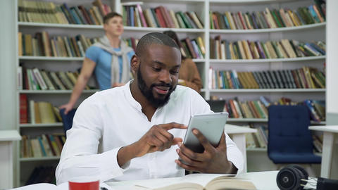 Close up of likable smiling positive bearded black-skinned guy which browsing Live Action