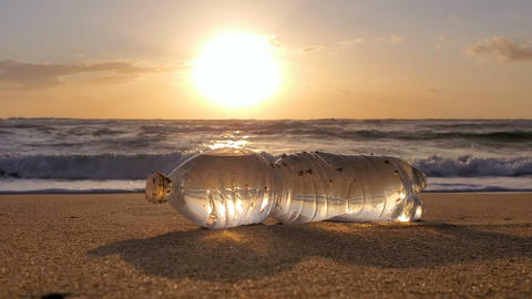 Transparent Plastic bottle on sandy sea shore motion sunset,polluted nature 4k Live Action