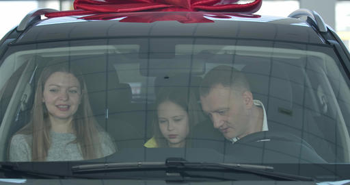 Close-up of happy successful Caucasian family buying vehicle in dealership Live Action