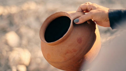 A woman pours sand from an empty jug. The concept of economical use of water Live Action