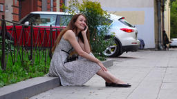 Brunette woman sit on border stone in city downtown talk cell phone Footage