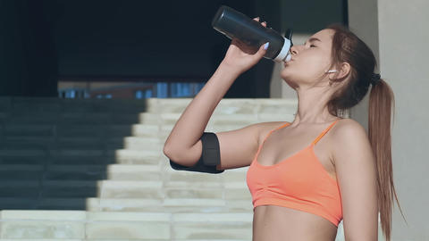 sporty girl drinks water and pours on face after workout Live Action
