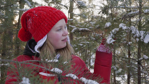 Happy playful girl enjoying hot drink in winter forest Live Action