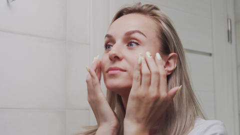 Woman applying cream and looking in mirror enjoy natural beauty and healthy Live Action