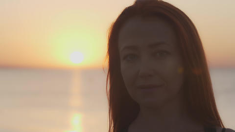 Portrait of a woman against the background of dawn over the sea Live Action
