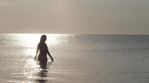 A beautiful woman in a swimsuit stands in the middle of a calm sea at dawn. The GIF