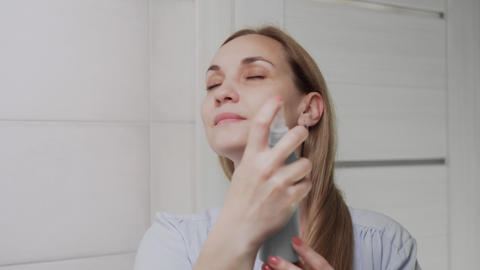 Close up Adult woman applying water spray for skin hydration Live Action