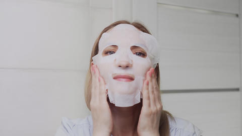 Close up of Adult woman applying mask on her face and looking at the camera Live Action