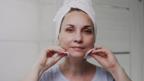 Adult woman with a towel on her head applying cream and looking at the camera Live Action