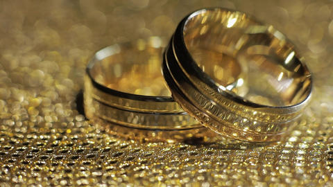 Wedding gold rings lying on shiny glossy surface. Shining with light. Close-up Live Action
