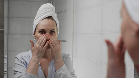 Frustrated Adult woman with a towel on her head looks at her face in the Live Action