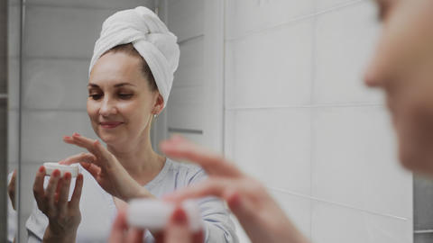 Adult woman with a towel on her head applying cream and looking in mirror enjoy Live Action