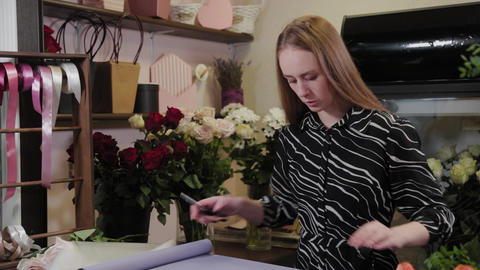 Professional florist prepares packaging for flowers. Beautiful bouquet for Live Action