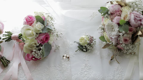 Beautiful wedding bouquets lie with wedding rings near window on white curtains Live Action