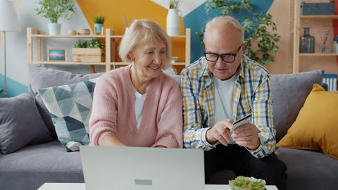 Cheerful elderly people making online payment with bank card using laptop at Live Action