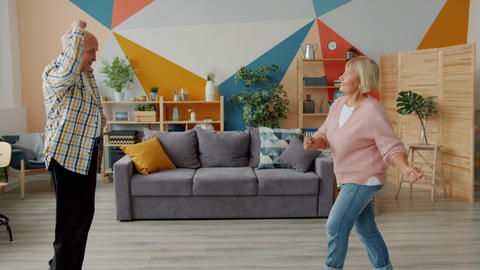 Carefree senior people couple dancing at home relaxing having fun with modern Live Action