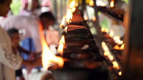 Closeup 4k video of burning oil lamps and worshipping religious people in altar Live Action