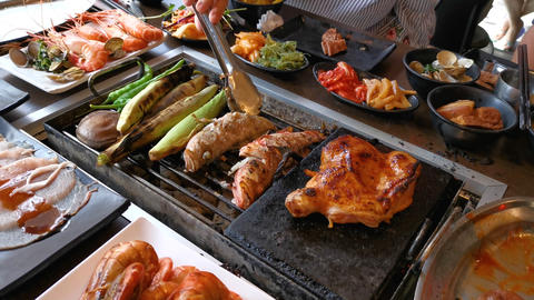 BBQ chicken and seafood on grill at restaurant Live Action