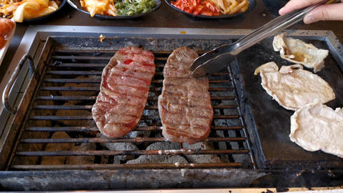 BBQ beef and pork on grill at restaurant Live Action