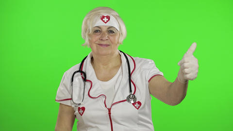 Elderly caucasian female doctor. Female nurse. Show OK sign. Thumbs up Live Action