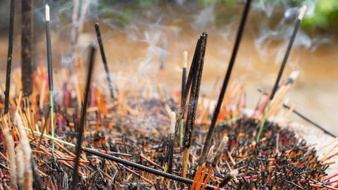 Closeup 4k video of aromatic smoke flowing from burning incense sticks on altar Live Action
