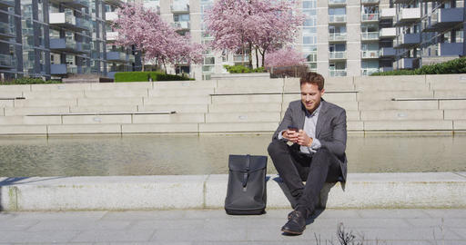 Smartphone - Young urban professional business man using phone relaxing in city Live Action