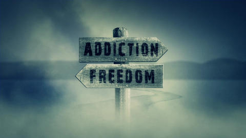 Old Wooden Sign on a Middle of a Cross Road With the Words Addiction or Freedom Footage