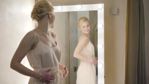 Back view of elegant young lady enjoying reflection in mirror in dressing room Live Action