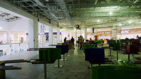 workers mount comfortable food court in shopping mall hall Live Action
