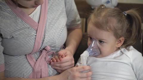 Little girl makes inhalation using a compressor inhaler while sitting on a sofa Live Action