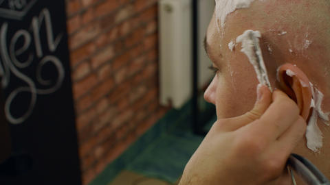 Close up shaving head of bald man with straight razor in barber salon. Barber Live Action