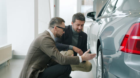 Slow motion of men client and salesman discussing car in showroom looking at Live Action
