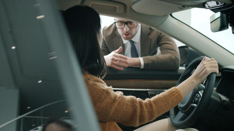 Young businesswoman talking to car dealer sitting inside new auto indoors Live Action