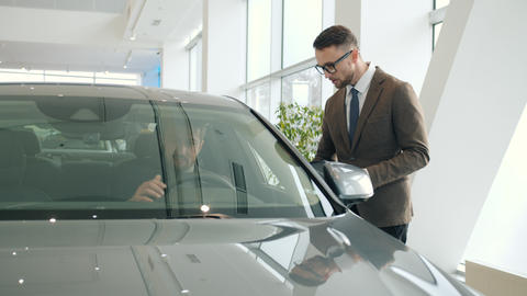 Sales manager talking to client sitting in car in showroom choosing automobile Live Action